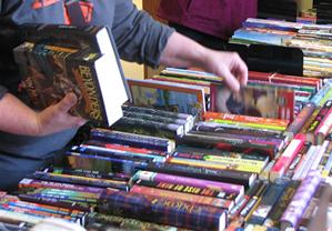 A woman searches through a box of books.